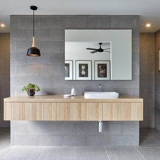 Modelo de cuarto de baño moderno con armarios con paneles lisos, puertas de armario de madera clara, baldosas y/o azulejos grises, lavabo sobreencimera, encimera de madera y ducha abierta
