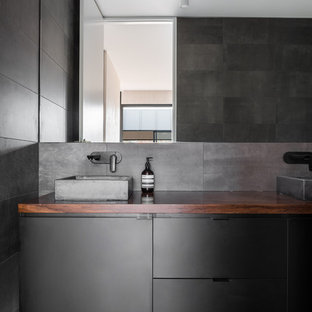 Photo of a mid-sized industrial bathroom in Perth with flat-panel cabinets, black cabinets and wood benchtops.