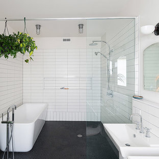 Example of an urban black and white tile mosaic tile floor and black floor bathroom design in Philadelphia with a wall-mount sink and white walls