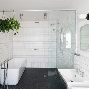 Foto de cuarto de baño urbano con lavabo suspendido, bañera exenta, ducha abierta, paredes blancas, suelo con mosaicos de baldosas, baldosas y/o azulejos blancas y negros, suelo negro y ducha abierta