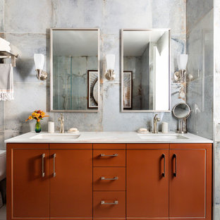 Photo of a mid-sized transitional master bathroom in New York with a bidet, blue tile, porcelain tile, blue walls, marble floors, marble benchtops, white floor, white benchtops, flat-panel cabinets, orange cabinets and an undermount sink.