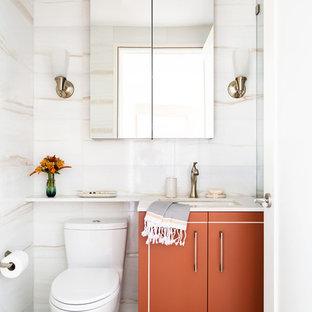 Aménagement d'une petit salle de bain classique avec un carrelage blanc, du carrelage en marbre, un mur blanc, un sol en carrelage de porcelaine, un sol bleu, une cabine de douche à porte battante, un plan de toilette blanc, un placard à porte plane, des portes de placard oranges et un lavabo encastré.