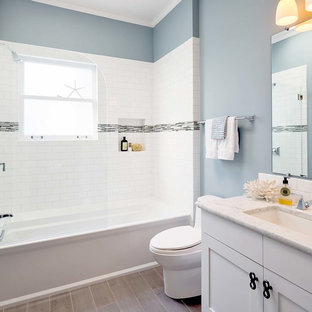 Photo of a small beach style master bathroom in San Francisco with an undermount sink, shaker cabinets, white cabinets, marble benchtops, an alcove tub, white tile, subway tile, blue walls, porcelain floors, a shower/bathtub combo, a one-piece toilet, green floor, a hinged shower door and white benchtops.