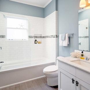 Imagen de cuarto de baño principal, costero, pequeño, con lavabo bajoencimera, armarios estilo shaker, puertas de armario blancas, encimera de mármol, bañera empotrada, baldosas y/o azulejos blancos, baldosas y/o azulejos de cemento, paredes azules, suelo de baldosas de porcelana, combinación de ducha y bañera, sanitario de una pieza, suelo verde, ducha con puerta con bisagras y encimeras blancas