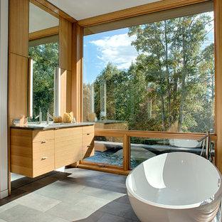 Foto di una stanza da bagno padronale moderna con ante lisce, ante in legno scuro, vasca freestanding, piastrelle grigie, pavimento grigio, pareti beige, pavimento con piastrelle in ceramica, lavabo integrato e top in cemento
