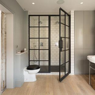 Idéer för att renovera ett mellanstort funkis en-suite badrum, med släta luckor, grå skåp, en kantlös dusch, en toalettstol med hel cisternkåpa, tunnelbanekakel, grå väggar, ljust trägolv, ett piedestal handfat, beiget golv och dusch med gångjärnsdörr