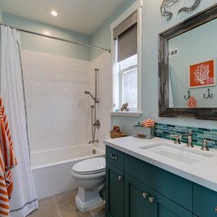 ロサンゼルスの小さいビーチスタイルのおしゃれな子供用バスルーム (シェーカースタイル扉のキャビネット、ターコイズのキャビネット、アルコーブ型浴槽、アルコーブ型シャワー、一体型トイレ、青いタイル、磁器タイル、青い壁、ライムストーンの床、アンダーカウンター洗面器、珪岩の洗面台、ベージュの床、シャワーカーテン) の写真