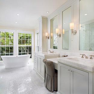 Ispirazione per una stanza da bagno padronale tradizionale con ante in stile shaker, ante grigie, vasca freestanding, pareti beige, lavabo sottopiano, pavimento bianco e top beige