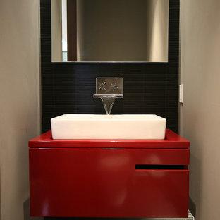 Exemple d'une salle de bain tendance avec une vasque, des portes de placard rouges, un carrelage noir et un plan de toilette rouge.