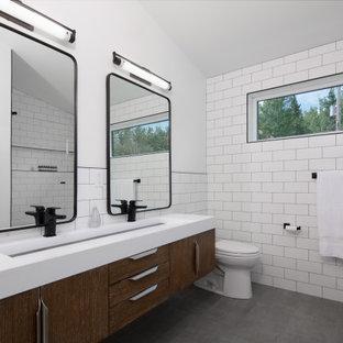 Cette photo montre une salle de bain tendance avec un placard à porte plane, des portes de placard en bois sombre, un carrelage blanc, un mur blanc, une grande vasque, un sol gris, un plan de toilette blanc, meuble double vasque, meuble-lavabo suspendu et un plafond voûté.