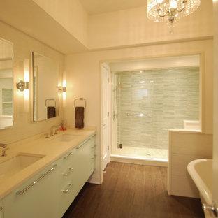 Immagine di una stanza da bagno classica con lavabo sottopiano, ante lisce, ante verdi, top in pietra calcarea, vasca freestanding e piastrelle verdi