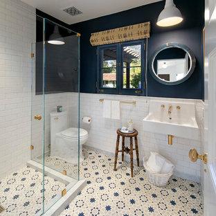 Foto di una stanza da bagno con doccia mediterranea di medie dimensioni con doccia ad angolo, WC monopezzo, piastrelle bianche, piastrelle in ceramica, pareti blu, lavabo sospeso, pavimento blu e porta doccia a battente