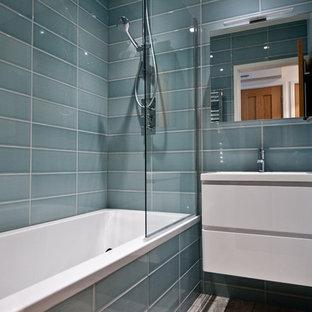Foto de cuarto de baño infantil, minimalista, pequeño, con armarios con paneles lisos, puertas de armario blancas, bañera encastrada, combinación de ducha y bañera, sanitario de una pieza, baldosas y/o azulejos grises, paredes grises, lavabo suspendido y baldosas y/o azulejos de cerámica