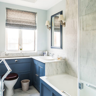 Small classic family bathroom in London with recessed-panel cabinets, blue cabinets, a built-in bath, a shower/bath combination, a two-piece toilet, white tiles, stone tiles, blue walls, marble flooring, a built-in sink and marble worktops.