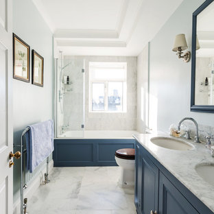 Design ideas for a mid-sized transitional master bathroom in London with recessed-panel cabinets, blue cabinets, a drop-in tub, a shower/bathtub combo, white tile, stone tile, blue walls, marble floors, an undermount sink and marble benchtops.
