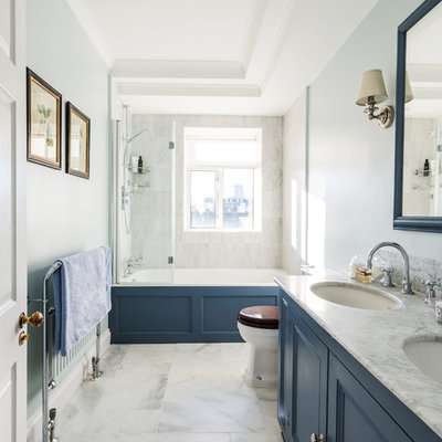 Mid-sized transitional master white tile and stone tile marble floor bathroom photo in London with recessed-panel cabinets, blue cabinets, blue walls, an undermount sink and marble countertops