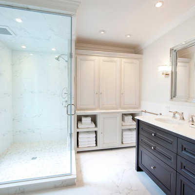 Inspiration for a mid-sized timeless master white tile and ceramic tile marble floor and white floor corner shower remodel in Philadelphia with an undermount sink, furniture-like cabinets, dark wood cabinets, a two-piece toilet, white walls, marble countertops and a hinged shower door