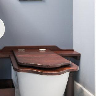 Foto de cuarto de baño con ducha, minimalista, de tamaño medio, con armarios estilo shaker, puertas de armario de madera oscura, bañera empotrada, ducha empotrada, bidé, baldosas y/o azulejos negros, azulejos en listel, paredes beige, suelo de madera clara, lavabo con pedestal y encimera de zinc