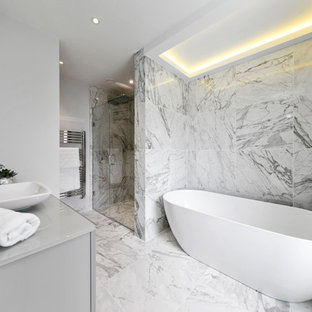 Design ideas for a medium sized modern bathroom in Surrey with flat-panel cabinets, a freestanding bath, a corner shower, marble tiles, grey walls, marble flooring, a vessel sink, white floors, a hinged door and grey worktops.