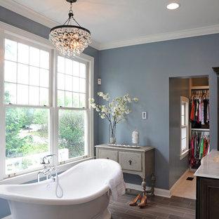 Modelo de cuarto de baño clásico con lavabo bajoencimera, puertas de armario de madera en tonos medios y bañera exenta