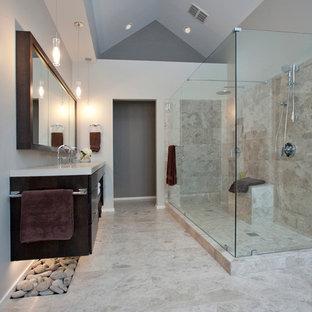 На фото: ванная комната в современном стиле с плоскими фасадами, темными деревянными фасадами, двойным душем, бежевой плиткой, столешницей из бетона, отдельно стоящей ванной и плиткой из известняка с