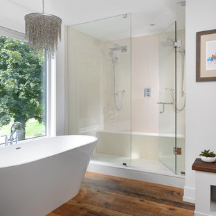 Design ideas for a contemporary master bathroom in Toronto with a freestanding tub, beige tile, white walls, medium hardwood floors, a double shower, flat-panel cabinets, white cabinets, a hinged shower door and a shower seat.
