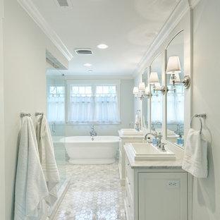 Immagine di una stanza da bagno padronale chic di medie dimensioni con vasca freestanding, piastrelle grigie, pareti grigie, pavimento in marmo, lavabo da incasso, top in marmo, pavimento bianco, porta doccia a battente, ante con riquadro incassato, ante bianche e top bianco