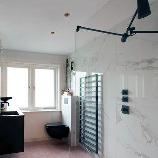 Modelo de cuarto de baño principal, minimalista, pequeño, con armarios con paneles lisos, puertas de armario negras, ducha abierta, sanitario de pared, baldosas y/o azulejos blancos, baldosas y/o azulejos de mármol, paredes blancas, suelo de azulejos de cemento, lavabo encastrado, encimera de granito y suelo rosa