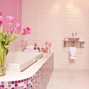 Example of a large trendy kids' mosaic tile and pink tile ceramic floor and white floor bathroom design in New York with pink walls, open cabinets, a one-piece toilet, a wall-mount sink and glass countertops