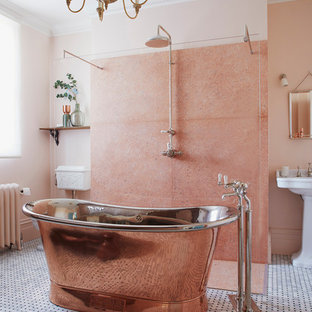 Large traditional family bathroom in London with freestanding cabinets, dark wood cabinets, a freestanding bath, a walk-in shower, a two-piece toilet, pink tiles, marble tiles, pink walls, mosaic tile flooring, a pedestal sink, black floors and an open shower.