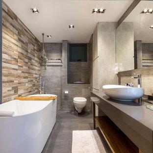 Modernes Badezimmer Mit Offenen Schränken, Freistehender Badewanne,  Wandtoilette, Grauen Fliesen, Grauer Wandfarbe