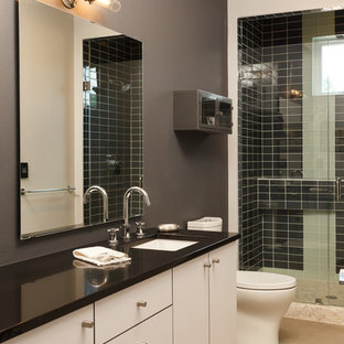 Esempio di una stanza da bagno industriale con lavabo sottopiano, piastrelle nere, piastrelle di vetro, pareti grigie e pavimento in cemento