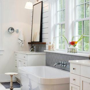 Inredning av ett klassiskt stort en-suite badrum, med ett undermonterad handfat, skåp i shakerstil, vita skåp, ett fristående badkar, grå kakel, tunnelbanekakel, vita väggar och bänkskiva i kvarts