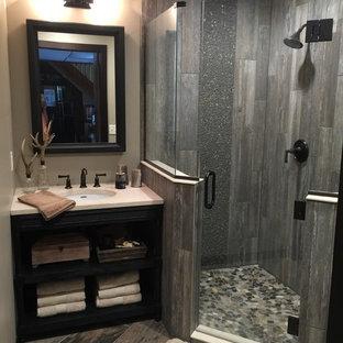 Rustik inredning av ett litet badrum med dusch, med ett undermonterad handfat, skåp i mörkt trä, bänkskiva i kvarts, en hörndusch, grå kakel, kakel i småsten, beige väggar, klinkergolv i keramik och öppna hyllor