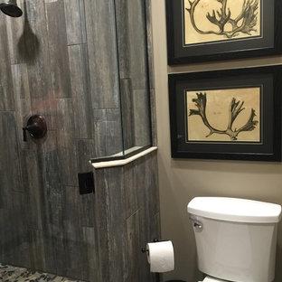 Imagen de cuarto de baño con ducha, rústico, pequeño, con lavabo bajoencimera, armarios tipo mueble, puertas de armario de madera en tonos medios, encimera de cuarzo compacto, ducha esquinera, sanitario de una pieza, baldosas y/o azulejos grises, suelo de baldosas tipo guijarro, paredes beige y suelo de baldosas de cerámica