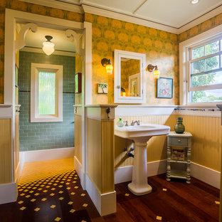 Imagen de cuarto de baño principal, de estilo americano, de tamaño medio, con paredes amarillas, suelo de madera oscura, lavabo con pedestal, baldosas y/o azulejos verdes y baldosas y/o azulejos de cemento