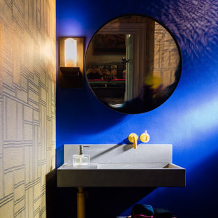 Photo of an eclectic bathroom in London with a wall-mount toilet, blue walls, a wall-mount sink, a single vanity and wallpaper.