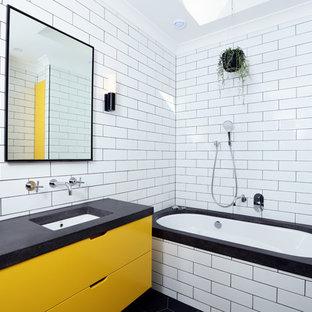 Ispirazione per una stanza da bagno contemporanea di medie dimensioni con vasca sottopiano, piastrelle diamantate, pavimento in gres porcellanato, top in cemento, ante lisce, ante gialle, lavabo sottopiano, pavimento nero e top grigio
