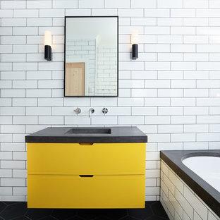 Modernes Badezimmer En Suite mit flächenbündigen Schrankfronten, gelben Schränken, Eckbadewanne, bodengleicher Dusche, weißen Fliesen, Metrofliesen, weißer Wandfarbe, Unterbauwaschbecken, Beton-Waschbecken/Waschtisch, schwarzem Boden und grauer Waschtischplatte in Melbourne