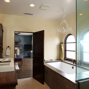 Inspiration for a large mediterranean ensuite bathroom in Los Angeles with beige walls, travertine flooring, wooden worktops, freestanding cabinets, distressed cabinets, a submerged bath, a double shower, a two-piece toilet, beige tiles, travertine tiles, a vessel sink, beige floors and a hinged door.