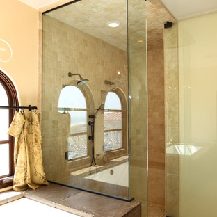 Inspiration for a large mediterranean master bathroom in Los Angeles with beige walls, travertine floors, furniture-like cabinets, distressed cabinets, an undermount tub, a double shower, a two-piece toilet, beige tile, travertine, a vessel sink, wood benchtops, beige floor and a hinged shower door.