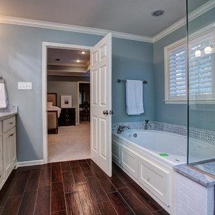 Foto di una stanza da bagno padronale classica di medie dimensioni con ante con bugna sagomata, ante bianche, vasca ad angolo, doccia aperta, WC monopezzo, piastrelle grigie, piastrelle bianche, pareti blu, parquet scuro, lavabo da incasso e top in acciaio inossidabile