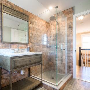 フィラデルフィアの小さいラスティックスタイルのおしゃれなバスルーム (浴槽なし) (レイズドパネル扉のキャビネット、茶色いキャビネット、コーナー設置型シャワー、赤い壁、クッションフロア、ペデスタルシンク、大理石の洗面台、茶色い床、開き戸のシャワー) の写真