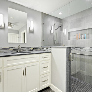 Example of a small transitional gray tile and porcelain tile porcelain floor corner shower design in Austin with an undermount sink, shaker cabinets, white cabinets, limestone countertops, a one-piece toilet and gray walls