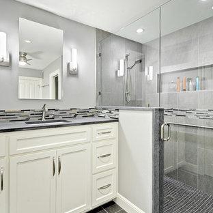 オースティンの小さいトランジショナルスタイルのおしゃれな浴室 (アンダーカウンター洗面器、シェーカースタイル扉のキャビネット、白いキャビネット、ライムストーンの洗面台、一体型トイレ、グレーのタイル、磁器タイル、グレーの壁、磁器タイルの床、コーナー設置型シャワー) の写真