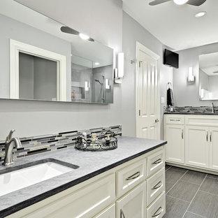 オースティンの小さいトランジショナルスタイルのおしゃれな浴室 (アンダーカウンター洗面器、レイズドパネル扉のキャビネット、白いキャビネット、珪岩の洗面台、グレーのタイル、セラミックタイル、グレーの壁、磁器タイルの床、コーナー設置型シャワー) の写真
