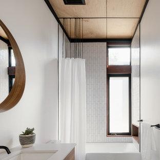 Cette photo montre une salle d'eau scandinave avec un placard à porte plane, des portes de placard en bois brun, une baignoire en alcôve, un combiné douche/baignoire, un carrelage blanc, un carrelage métro, un mur blanc, un lavabo encastré, un sol noir, une cabine de douche avec un rideau, un plan de toilette blanc, meuble simple vasque et un plafond en bois.