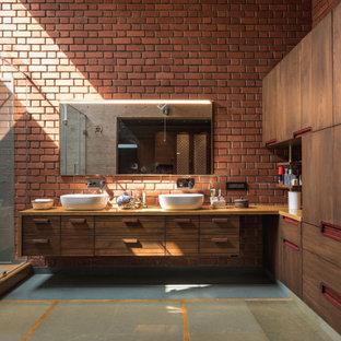 На фото: огромная главная ванная комната в стиле лофт с плоскими фасадами, фасадами цвета дерева среднего тона, угловым душем, красными стенами, настольной раковиной, столешницей из дерева, серым полом, душем с распашными дверями, коричневой столешницей, тумбой под две раковины, подвесной тумбой и кирпичными стенами с