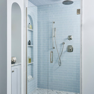 Example of a transitional 3/4 blue tile gray floor alcove shower design in Minneapolis with blue cabinets and a hinged shower door