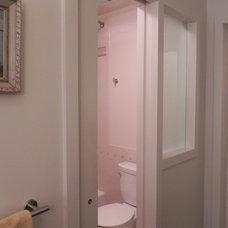Eclectic Bathroom pocket door, frosted window separating toilet in narrow bathroom